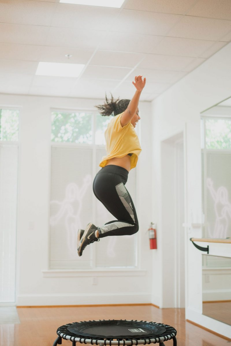woman bouncing in air on trampoline